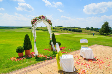 Arch and two white chairs prepared for weeding ceremony, Poland