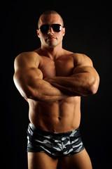 Handsome muscular man in sunglasses posing