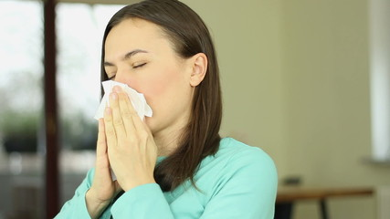 Young woman having a flu and sneezing, close up