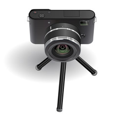 Digital photo camera on small tripod.