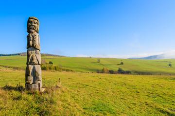 Wooden sculpture on meadow in autumn, Beskid Niski Mountains