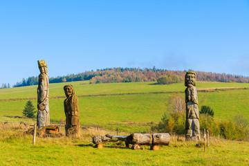 Wooden sculptures on meadow in autumn, Beskid Niski Mountains