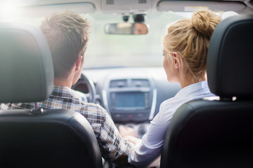 handsome couple in a car, view from rear seat