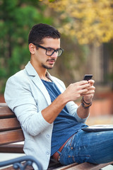 Young businessman using smart phone and laptop outdoors