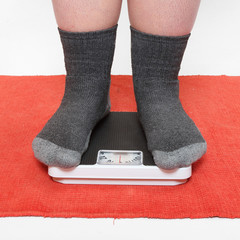 Overweight woman standing on a weighing machine.