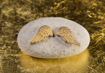 Trauer oder Liebe: zwei Flügel eines Engels auf einem Stein