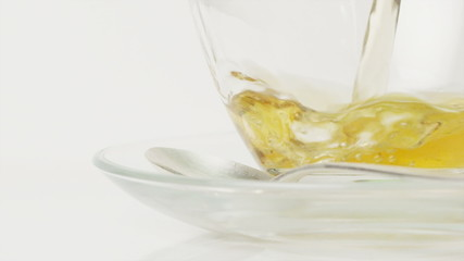 Tea being poured into a clear glass cup in slow motion