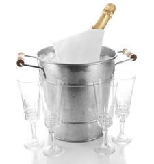 Bottle of champagne in metal ice bucket and empty glasses
