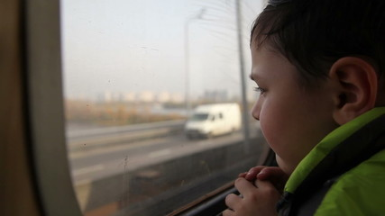 boy looking out the window at the cars in the metro 3