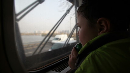 boy looking out the window at the cars in the metro 2