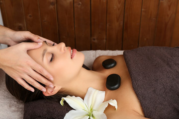 Beautiful young woman in spa salon with spa stones taking head