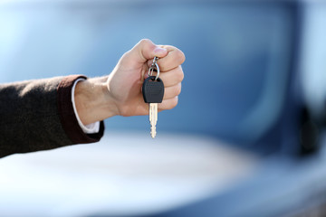 Businessman holding car key outdoors