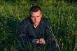 Hombre Joven pensativo sentado en la hierba  y luz de atardecer