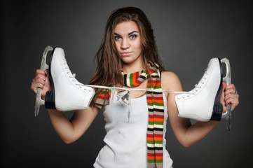 The beautiful young girl posing with skates - isolated