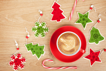 Christmas decor and coffee cup over wooden table background