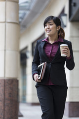 Asian business woman standing outside in modern city.
