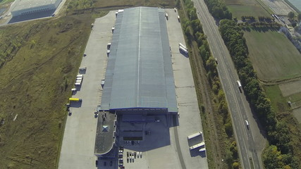 Up over Cargo  warehouse  and highway with cars . Aerial