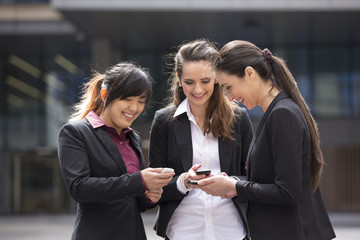 Three happy Business women looking at there mobile phones.