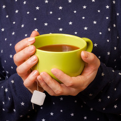 Woman hands holding a cup of tea