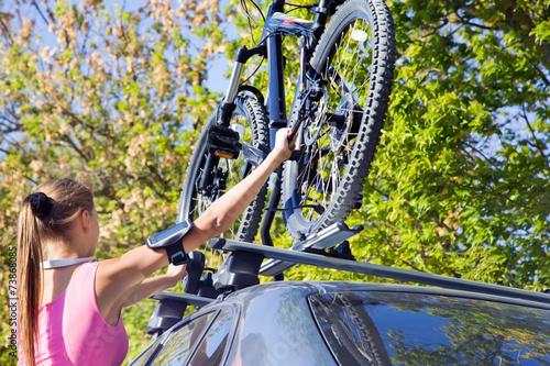 Leinwandbild Motiv Girl mounted  transportation bikes on the roof of a car
