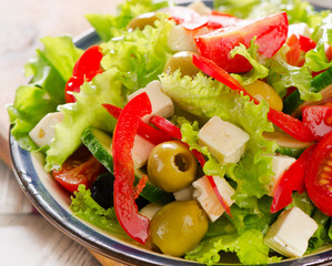 Fresh   salad with feta cheese and olives  .
