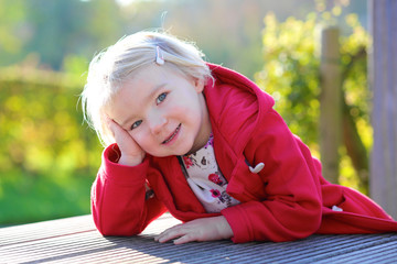 Portrait of beautiful toddler girl in red duffle coat outdoors
