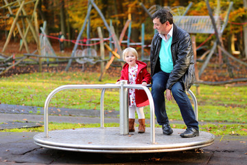 Father and little daughter having fun at playground