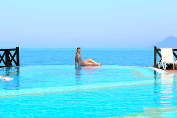 Beautiful woman relaxing at the edge of infinity pool