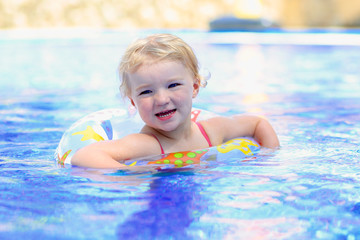 Happy little girl relaxing in the pool with inflatable ring