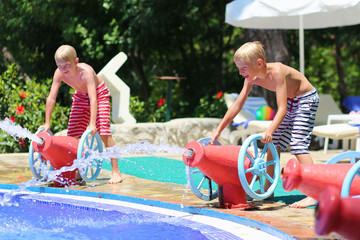 Happy boys having fun on water slide in a outdoors swimming pool