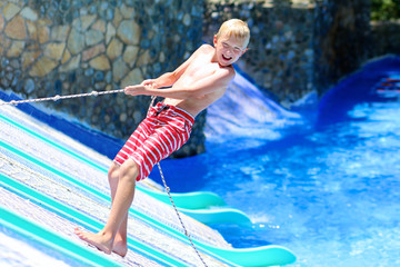 Happy boy having fun on water slide in a outdoors swimming pool