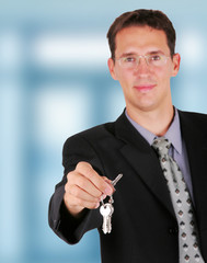 Businessman holding key in his hand to hand it over