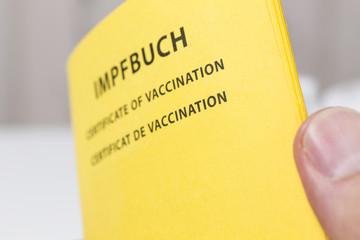 Männliche Hand hät Impfbuch, Freiburg, Deutschland