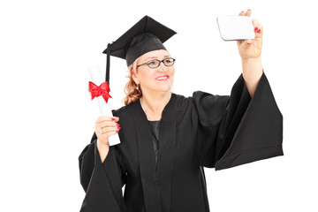 Mature female graduate taking a selfie with cell phone