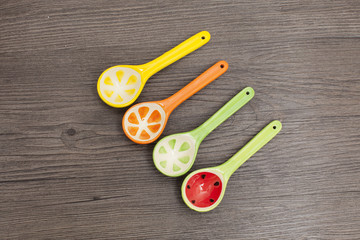 Spoons of different colors on wood background