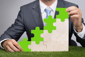 Businessman Holding Jigsaw Graph On Grass