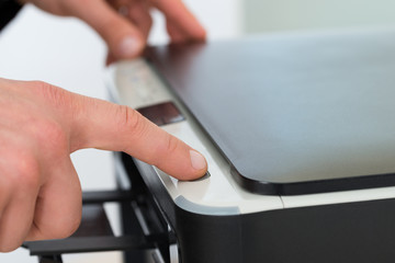 Businessman's Finger Pressing Button Of Photocopy Machine