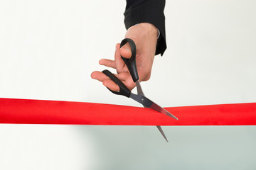 Businessman Cutting Red Ribbon With Scissors