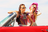 Beautiful ladies with sun glasses posing in a vintage retro car