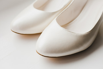 White elegant bridal shoes on the floor