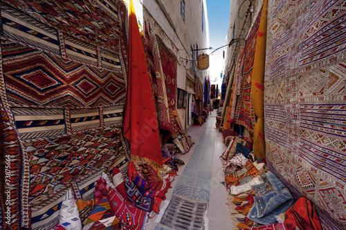 Gasse mit Teppichhändlern in Essaouira, Marokko - 73875664