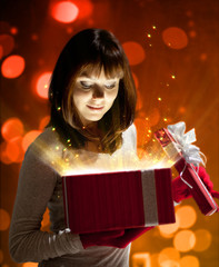 Young woman keeps Christmas red gift with magic light.