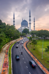 A mosque and a cloudy sunrise with cars moving on roads