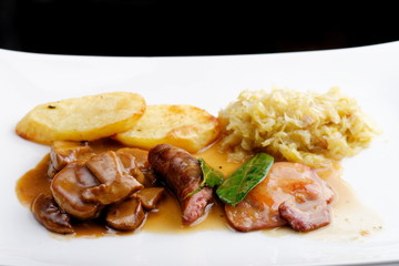 German food,  with sausages, steaks, potato and cabbage