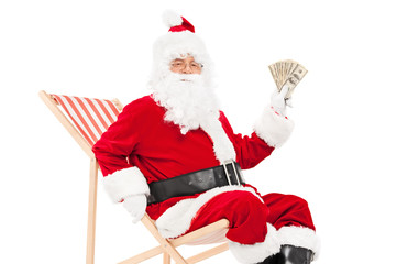 Santa holding money seated in a lounger chair