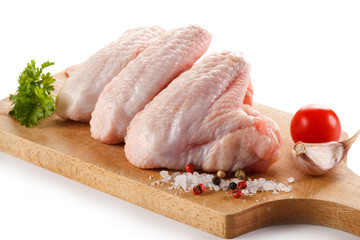 Raw chicken wings on cutting board on white background