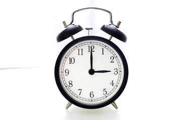 Oldfashioned black glossy alarm clock showing 3 o'clock