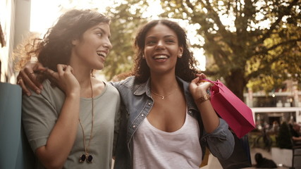 Mixed race girl friends walking in city urban area with shopping