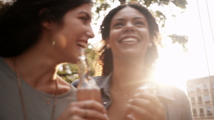Mixed race Girl friends enjoying pink lemonade drinks together o