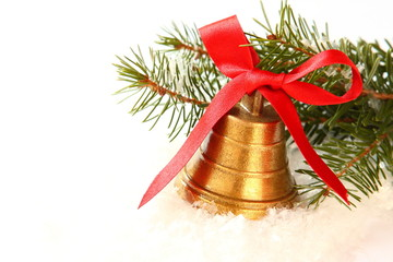 Golden bell with red bow and branch of christmas tree